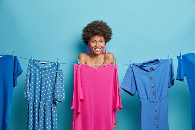 Frau mit lockigem haar steht schüchtern versteckt nackten körper hinter einem kleid auf der wäscheleine lächelt glücklich und zieht sich zu einem besonderen ereignis isoliert auf blau an