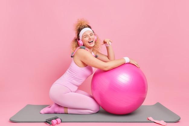 Frau mit lockigem haar stützt sich auf fitnessball und ist gut gelaunt hört musik über drahtlose kopfhörerübungen auf der matte