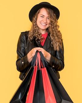 Frau mit lockigem haar und taschen am schwarzen freitag-verkauf