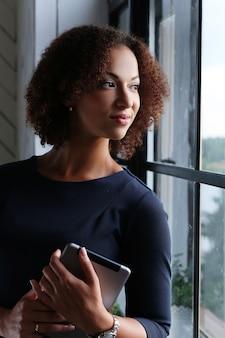 Frau mit lockigem haar unter verwendung einer tablette