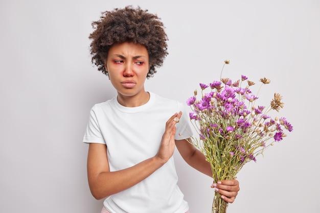 Frau mit lockigem haar weigert sich, einen strauß wildblumen zu bekommen, die gegen pollen allergisch ist, sieht unglücklich aus, hat rote augen und eine lässig gekleidete nase, die an der weißen wand posiert