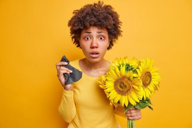 Frau mit lockigen haaren, roten, geschwollenen augen, hält serviettenniesen wegen sonnenblumenallergie, die krank ist, posiert drinnen auf leuchtendem gelb