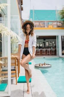 Frau mit lockiger frisur, die im resort aufwirft. volle länge schuss der glücklichen gebräunten frau in der badebekleidung, die nahe pool steht.