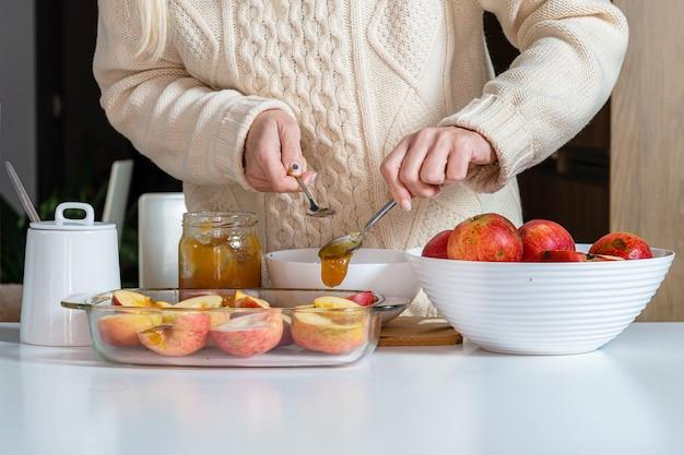Frau mit löffel, der äpfel mit honig in einem glasbehälter gießt und sie für das kochen vorbereitet, hausgemachtes wüstenbackkonzept