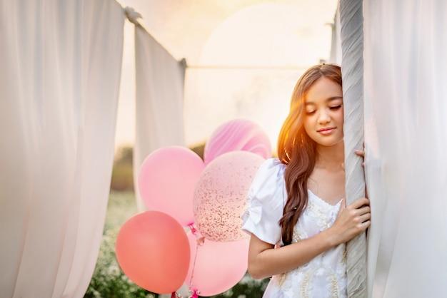 Frau mit luftballons, die draußen aufwerfen