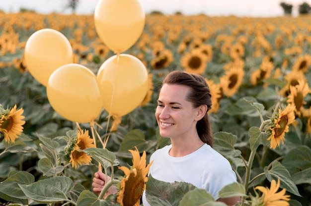 Frau mit luftballons im sonnenblumenfeld