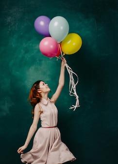 Frau mit luftballons in ihren händen, die ein kleid tragen