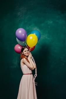 Frau mit luftballons in ihren händen, die ein rosa kleid tragen