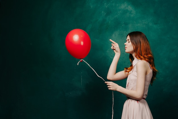 Frau mit luftballons in ihren händen in einem kleid, studio