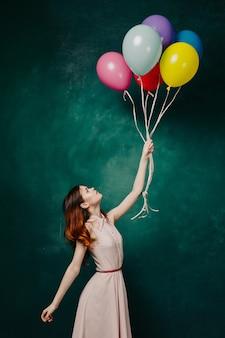 Frau mit luftballons in ihren händen in einem kleid