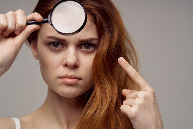 Frau mit lupe in der nähe von gesicht pickel fenster gesundheitsprobleme