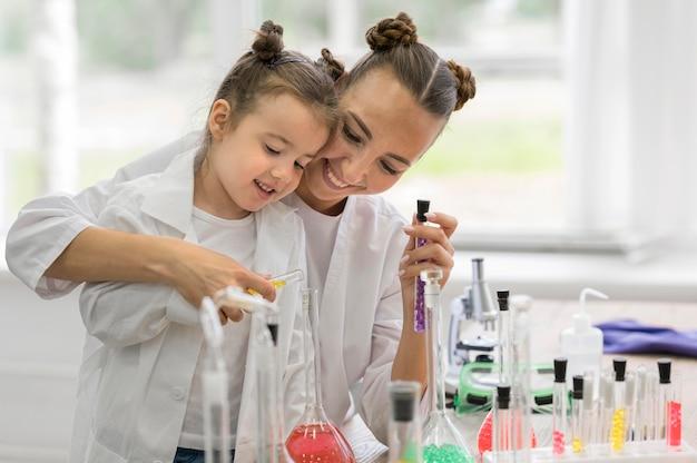 Frau mit mädchen im labor, das experimente macht