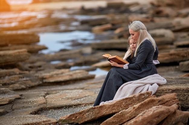 Frau mit mädchenlesebuch auf küste
