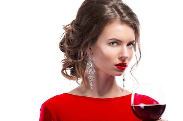 Frau mit make-up, frisur, die rotes kleid schwärmt, das mit glas weinstock über weißem hintergrund aufwirft, isolieren.