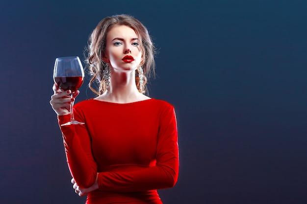 Frau mit make-up, frisur, die rotes kleid trägt, das mit glas weinstock über dunklem hintergrund aufwirft