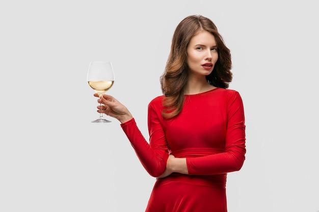 Frau mit make-up, frisur, die rotes kleid trägt, das mit glas weinstock über weißer wand aufwirft, isolieren.