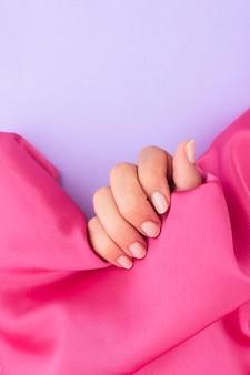 Frau mit maniküre getan, die ein rosa tuch mit kopienraum hält