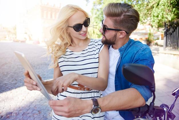Frau mit mann, der digitales tablett an der stadtstraße verwendet