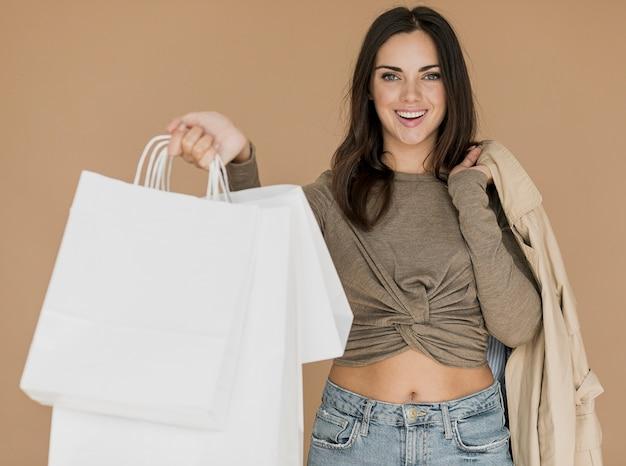 Frau mit mantel auf schulter und weißen einkaufstüten