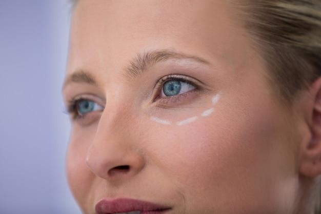Frau mit markierungen für kosmetische behandlung gezeichnet