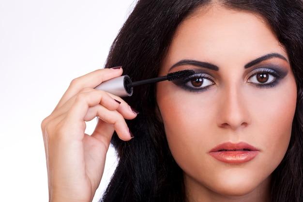 Frau mit mascara-pinsel in der hand