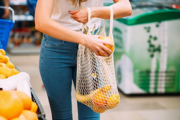 Frau mit maschentasche voll vom frischgemüse, das im geschäft, nullabfallkonzept, eco freundlich kauft