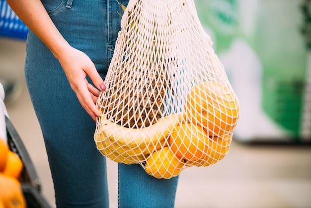 Frau mit maschentasche voll vom frischgemüse, das im geschäft, nullabfallkonzept kauft