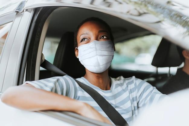 Frau mit maske beim durchfahren mit ihrem auto