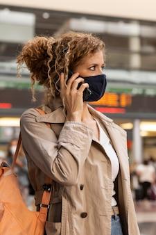 Frau mit maske, die am telefon spricht