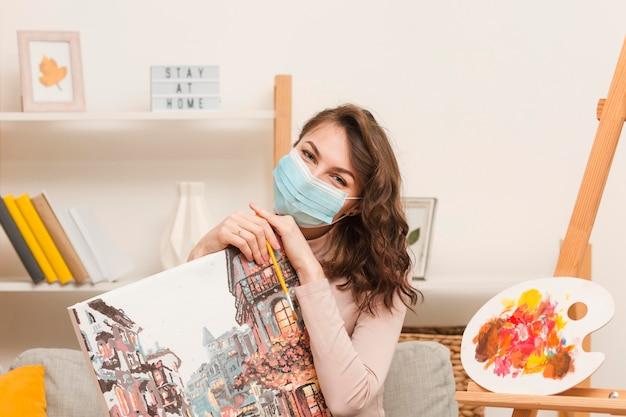Frau mit maske, die bild hält