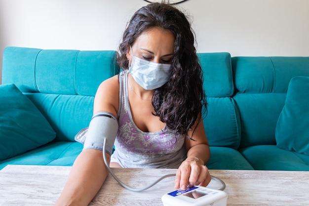 Frau mit maske, die blutdruck zu hause nimmt