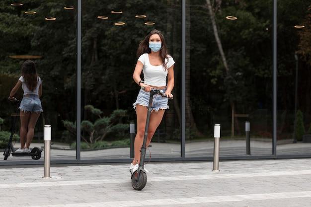 Frau mit maske, die einen elektroroller reitet