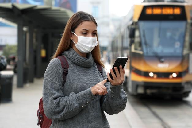 Frau mit maske, die für online-transportticket über app auf smartphone kauft und bezahlt
