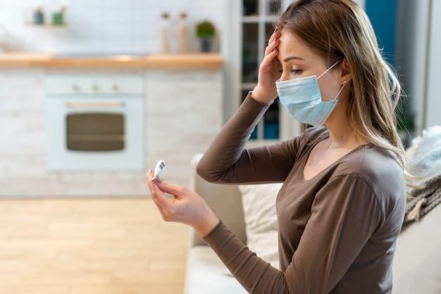 Frau mit maske, die in der quarantäne bleibt, die ihre temperatur prüft