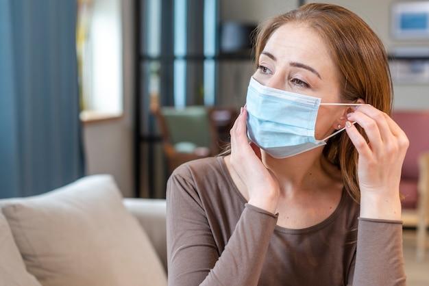 Frau mit maske, die in der quarantäne bleibt wegschaut