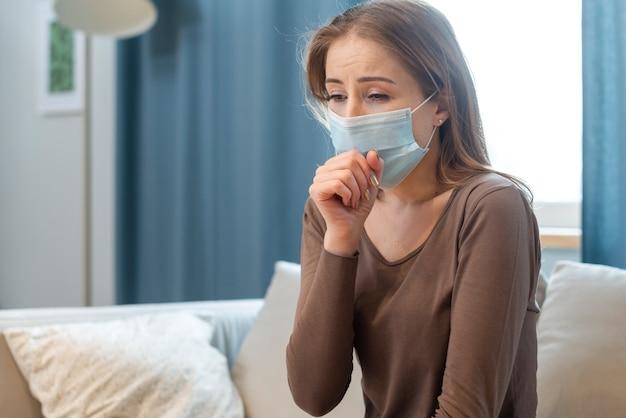 Frau mit maske, die in quarantäne bleibt und hustet