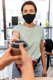 Frau mit maske, die kaffee kauft