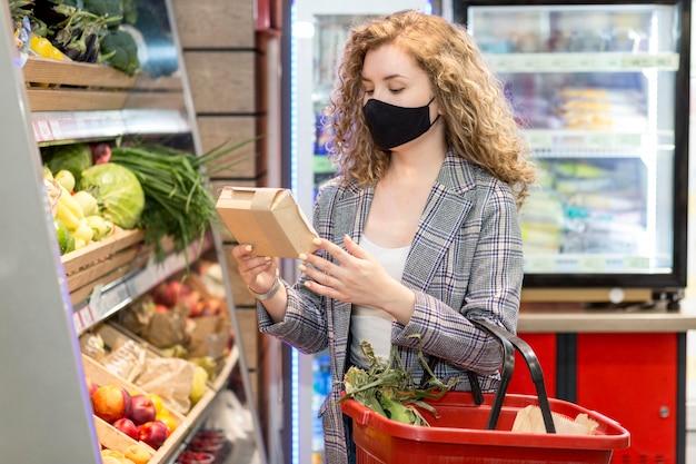 Frau mit maske, die lebensmittel kauft