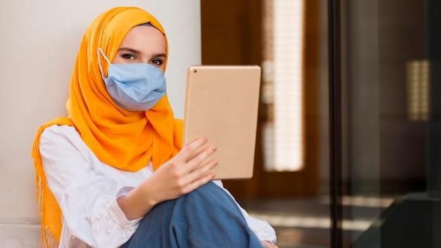 Frau mit maske, die tablette hält