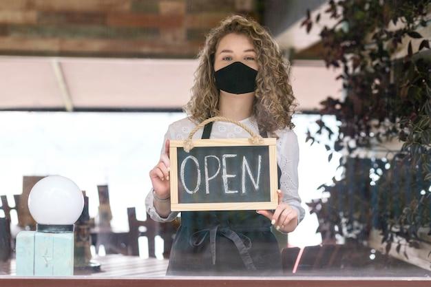 Frau mit maske, die tafel mit offenem text hält