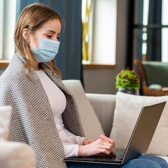 Frau mit maske, die von zu hause aus arbeitet