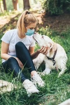 Frau mit maske genießt die zeit draußen mit ihrem hund