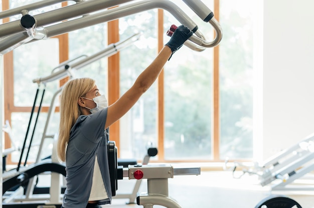 Frau mit maske im fitnessstudio unter verwendung der ausrüstung