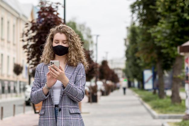 Frau mit maske im freien, die handy prüft
