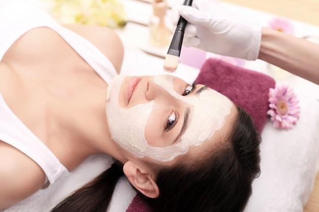 Frau mit maske im gesicht bei kopfmassage,