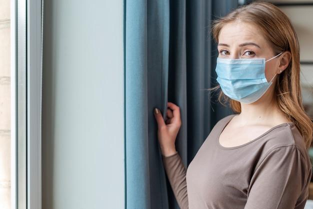 Frau mit maske im mittleren schuss der quarantäne
