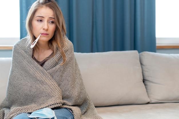 Frau mit maske in quarantäne, die auf einer couch sitzt