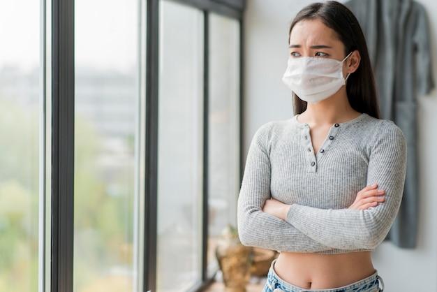 Frau mit maske stehend mit verschränkten armen
