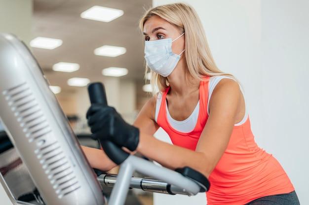 Frau mit maske und handschuhen, die an der turnhalle arbeiten