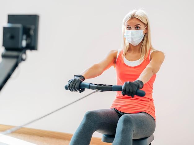 Frau mit maske und handschuhen im fitnessstudio trainieren